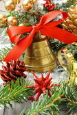 Golden bell with red ribbon bow and christmas decoration — Stock Photo