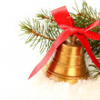 Golden bell with red bow and branch of christmas tree — Stock Photo #32586587