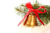 Golden bell with red bow and branch of christmas tree — Stock Photo