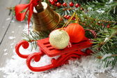 Christmas composition with sleigh, pinecone and bell — Stock Photo