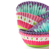 Colorful cupcake wrappers over white with copyspace — Stock Photo