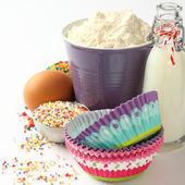 Cupcake cases and ingredients over white with copyspace — Stock Photo