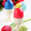 Colorful easter eggs and pink tulips on white wooden background — Stock Photo #36014181