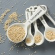 Foto Stock: Quinograin in porcelain measuring spoons on gray background