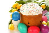 Easter bread, colorful eggs and yellow tulips on white background — Stock Photo