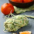 Ball of thread with knitting needle and fresh mandarins on gray background — Stock Photo