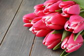 Beautiful pink tulips on wooden background — Стоковое фото