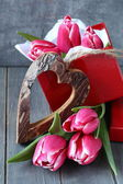 Beautiful pink tulips with gift box and wooden heart — Stock Photo