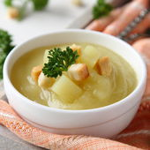Creamy sweet potato soup with croutons and parsley in white bowl — Stock Photo