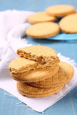 Stack of vanilla sandwich cookies on blue wooden background — Stock Photo