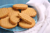 Sandwich biscuits with syrup filling on blue wooden background — Stock Photo