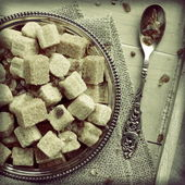 Heap of brown sugar cubes on metal plate on wooden tray — Stock Photo