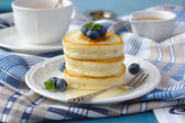 A stack of scotch pancakes with with honey and blueberries on a breakfast table — Stock Photo
