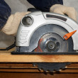 Foto Stock: Wood cutting with circular saw