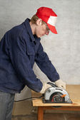 The worker operates circular saw — Stock Photo