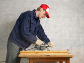 The worker operates electric planer — Stock Photo