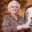 Senior woman shows her portrait - Stock Photo
