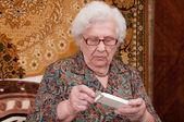 Senior woman takes out pills — Stock Photo