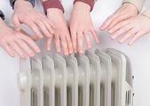 Familia calentando las manos sobre el calentador eléctrico — Foto de Stock