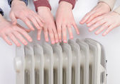 Family warming up hands over electric heater — Stok fotoğraf