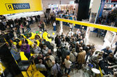 Visitors look at new products on Nikon stand at Consumer Electronics & Phot — Stock Photo