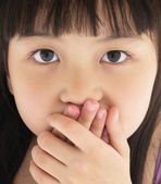 Scared little girl covering mouth with hand — Stock Photo
