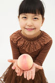 Asian little girl with peach — Stock Photo