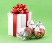 White gift box with red ribbon bow and christmas balls — Stock Photo