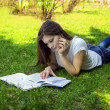 Student woman teaches from notes lying on the grass in the park — Stock Photo