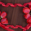 Tulip on wooden background with red ribbon — Stock Photo