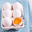 Six fresh eggs in egg holder with one cracked egg — Stock Photo
