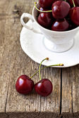 Sweet cherries in a white cup — Stock Photo