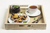 Black currant muffins with a cup of tea — Stock Photo