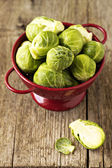 Brussels sprouts in a red colander — Stock Photo
