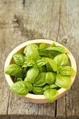 Leaves of fresh basil in a bowl on wooden table — Stock Photo