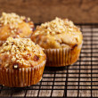Banana muffins with walnuts and white chocolate on a cooling rack — Stock Photo #20013509