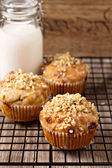 Banana muffins with walnuts and white chocolate and a bottle of milk on a cooling rack — Stock Photo
