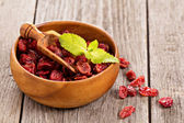 Dried cranberries in a wooden bowl — Stock Photo