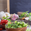 Green salad leaves in a wooden bowl — Stock Photo