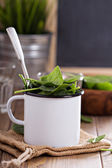Green spinach leaves in a mug — Stock Photo