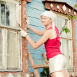 Portrait of smiling young woman making cosmetic alterations of house — Stock Photo