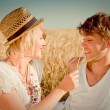 Image of young man and woman on wheat field — Stockfoto