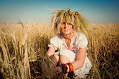 Beautiful girl in a traditional slavic wreath on a field of golden wheat — Stock Photo
