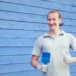 Man posing near house with painting brush — Stock Photo