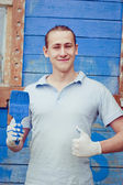 Man posing near house with painting brush — Stock Photo