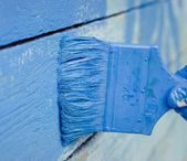 Hand painting blue wooden wall — Stock Photo