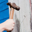 Hand with hammer on blue wooden background — Photo