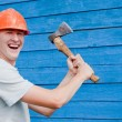 Stock Photo: Man with axe on blue wooden background