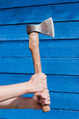 Hand with axe on blue wooden background — Stock Photo