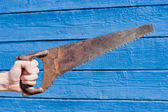 Hand with saw on blue wooden background — Stock Photo